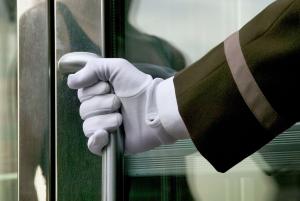 Doorman in uniform, opening door. Manhattan, New York. NYC